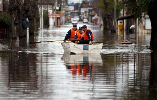 Deux policiers se déplacent en bateau dans la ville inondée de Lujan, en Argentine, le 12 août.
