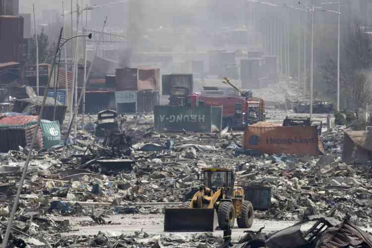 Un bulldozer déblaie un site à proximité du lieu de l'explosion. Selon la police locale, l'entrepôt où a eu lieu l'incendie appartient à l'entreprise Tianjin Dongjiang Port Rui Hai International Logistics. Les médias d'Etat ont annoncé l'arrestation de plusieurs cadres de l'entreprise.
