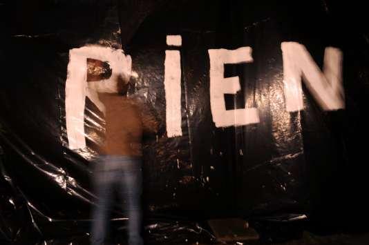 """Un éleveur écrit le mot """"RIEN"""" sur une bâche installée devant les bureaux du député Jean-Luc Bleuven lors d'un rassemblement de protestation d'éleveurs de porc à Plabennec le 12 août 2015."""