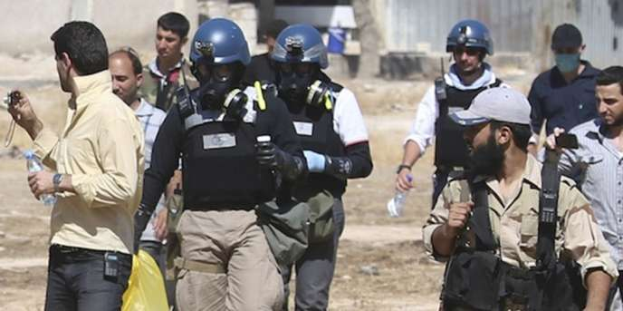 Des experts de l'OIAC, escortés par des combattants de l'Armée syrienne libre, transportent des échantillons collectés sur le site possible d'une attaque chimique à Damas, le 28 août 2013.
