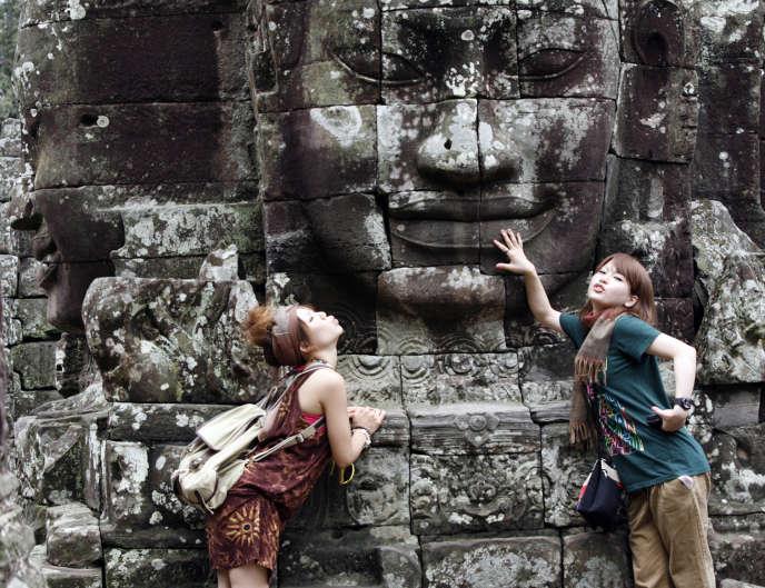 Des touristes posent devant l'un des temples d'Angkor dans la province de Siem Reap au Cambodge en octobre 2009.