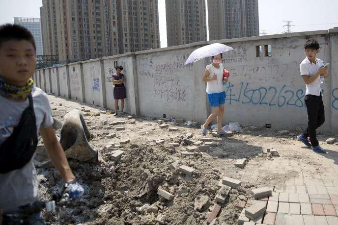 Des passants regardent des débris projetés dans les rues de Tianjin après les explosions sur le site portuaire, le 13 août 2015.