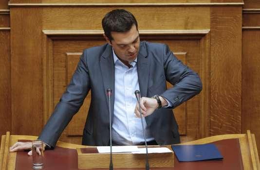 Le premier ministre grec, Alexis Tsipras, regarde sa montre au moment de conclure son discours devant le Parlement, vendredi 14 août.