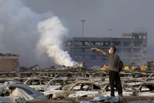 Un homme entouré de voitures calcinées après la double explosion à Tianjin, en Chine, le 12 août.