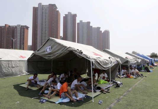 Des habitants s'abritent sous des tentes montées dans une école primaire dans le quartier de Binhai, près du site de la catastrophe industrielle, à Tianjin, le 13 août.