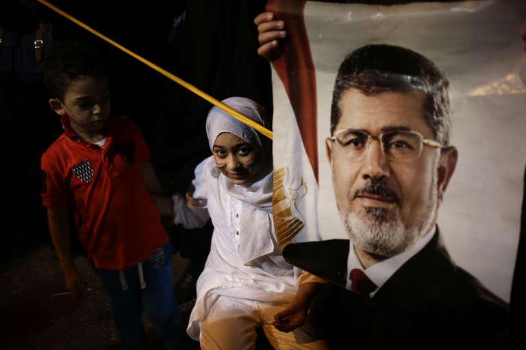Des enfants de partisans des Frères musulmans campent près d'un poster à l'effigie de le Mohammed Morsi, en juillet2013.