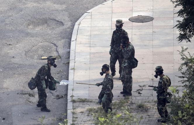 Des militaires inspectent les alentours du site des explosions, à Tianjin, le 15août.