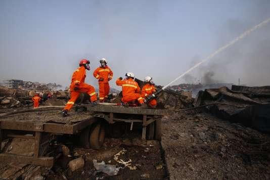 Des pompiers chinois à Tianjin, sur le site des explosions qui ont secoué la ville le 12août au soir.