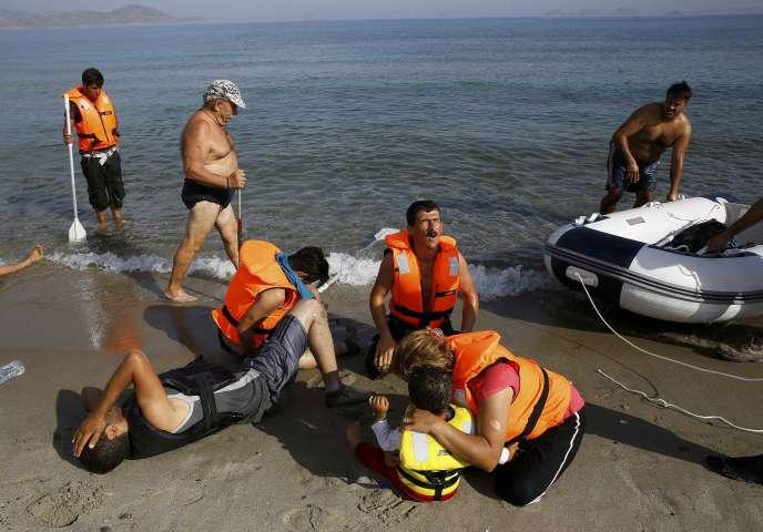 Sur une plage de l'île grecque de Kos, le 15 août 2015. Un touriste passe devant un groupe de migrants iraniens épuisés. Ces derniers viennent tout juste de débarquer de leur petite embarcation non motorisée.
