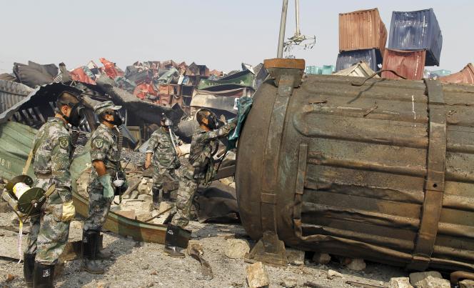 Des soldats chinois équipés de masques à gaz examinent un conteneur sur le site des explosions à Tianjin.