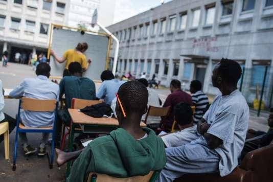 Un cours de français dispensé, le 6 août, aux migrants qui occupent l'ancien lycée Jean-Quarré à Paris.