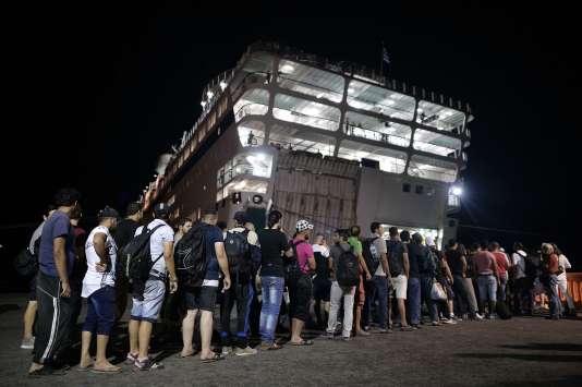 Des migrants syriens font la queue, le 17août, pour embarquer à bord du navire-hôtel «Eleftherios Venizelos», envoyé à Kos par Athènes pour servir de centre d'accueil temporaire.