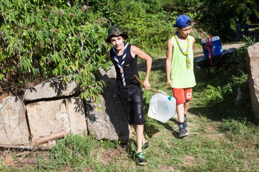 Des Scouts musulmans de France transportent de l'eau jusqu'au campement.