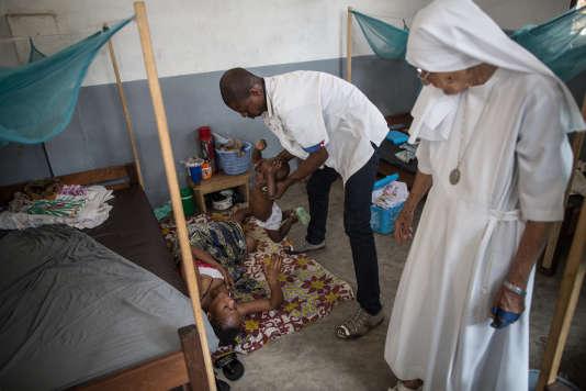 Un infirmier aide une femme souffrant d'une perforation de l'utérus suite à un avortement artisanal, à l'hôpital de Zongo, en République Démocratique du Congo le 21 juin 2015.