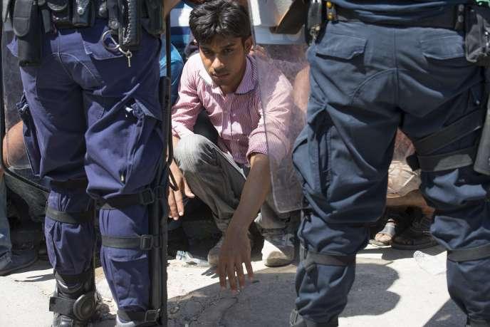 Des policiers encadrent des migrants qui attendent leur enregistrement auprès de l'administration, à Kos, le 19 août.