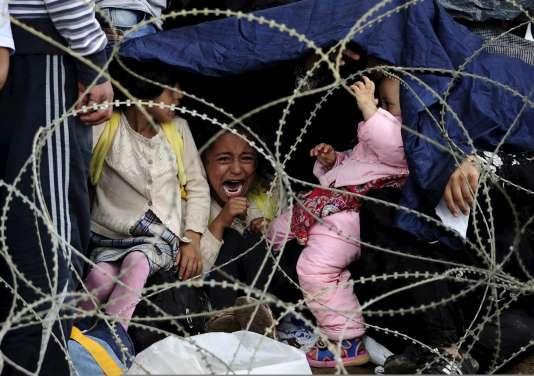 Des familles de réfugiés attendent sous la pluie de passer la frontière entre la Grèce et la Macédoine, samedi 22 août.