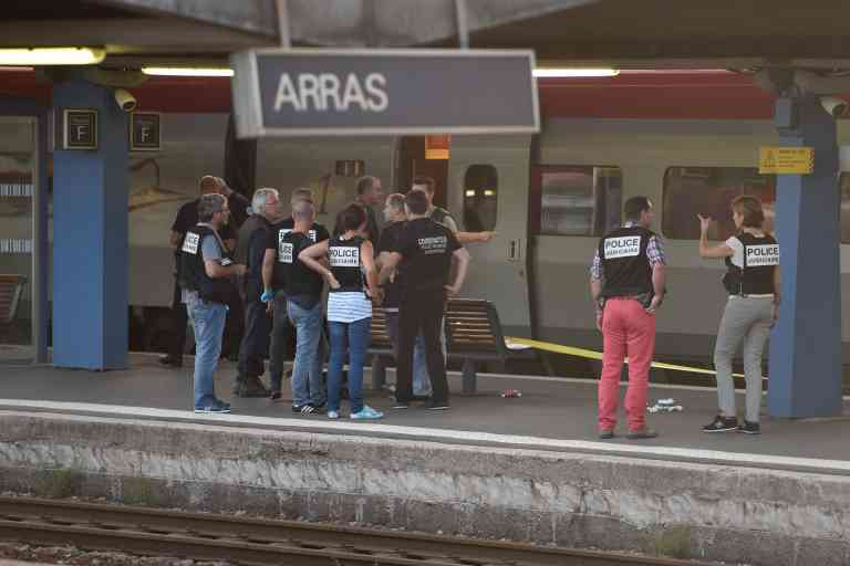 Crime and forensic investigators stand on a platform next to a Thalys train of French national railway operator SNCF at the main train station in Arras, northern France, on August 21, 2015. A gunman opened fire on a train travelling from Amsterdam to Paris, injuring three people before being overpowered by passengers, French state rail company SNCF and rescue services said. Two of the victims were seriously injured and at least one suffered gunshot wounds, an SNCF spokesman said, adding that the assailant was armed with guns and knives. The motives behind the attack were not immediately known. AFP PHOTO / PHILIPPE HUGUEN