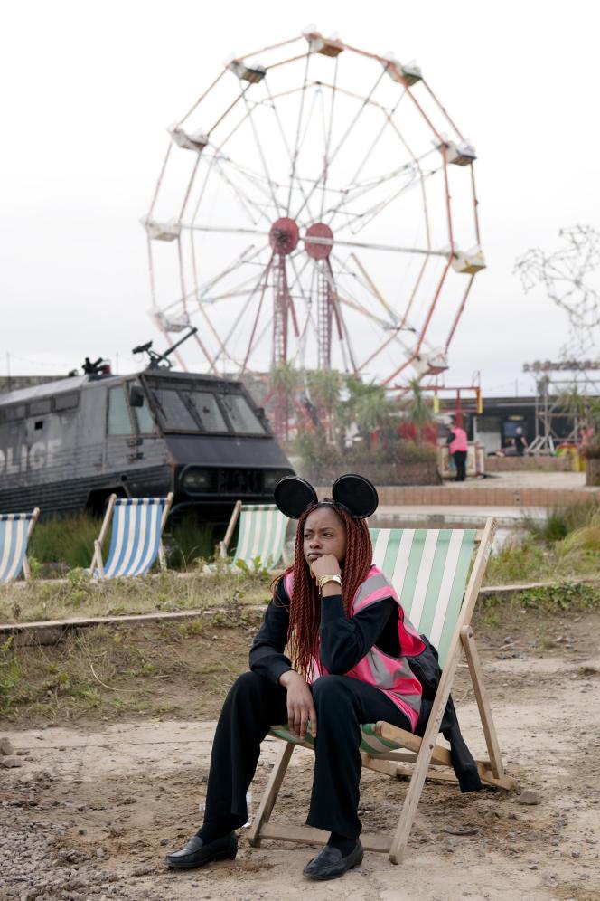 Une employée du parc devant la fontaine de Banksy, la grande roue et le cheval géant de Ben Long.