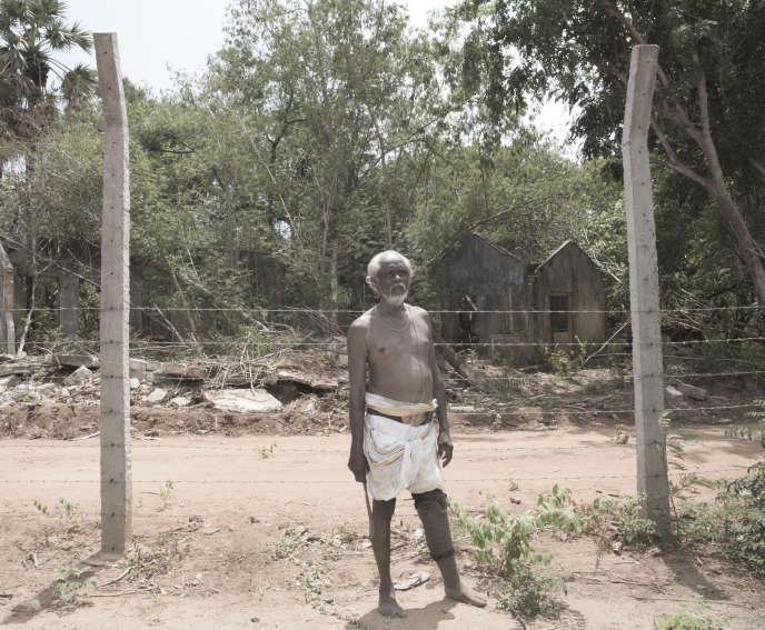 Subnamanigaiyar Kugathasasanma, devant sa maison en ruine, quittée dans la précipitation il y a vingt-cinq ans.