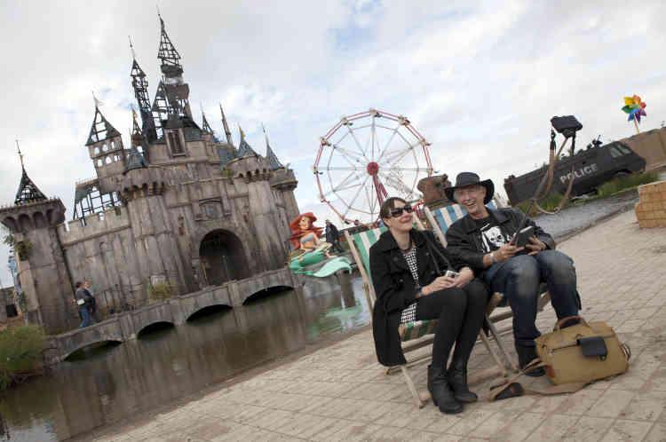 Des visiteurs se font prendre en photo devant le château.
