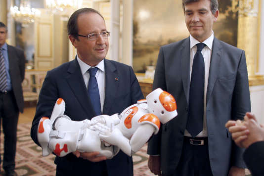 """François Hollande et Arnaud Montebourg. Le président tient dans ses bras """"Nao"""", le robot de la compagnie Aldebaran Robotics. Palais de l'Elysée, Paris, le 12 septembre 2013."""
