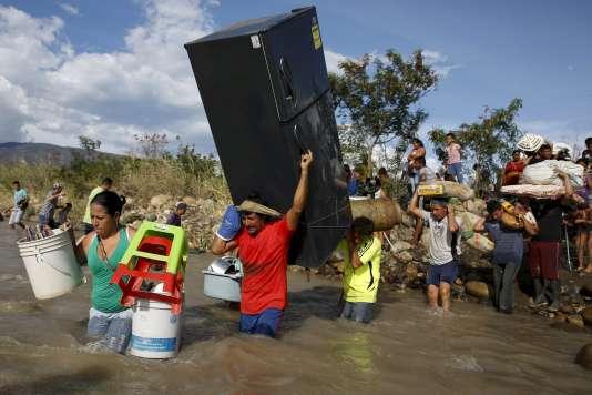 Des Colombiens quittent le Venezuela en traversant la rivière Tachira avec leurs biens, mardi 25août.