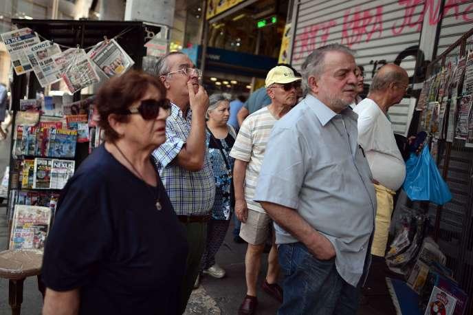 Des habitants d'Athènes lisent les gros titres des journaux le 21 août 2015.