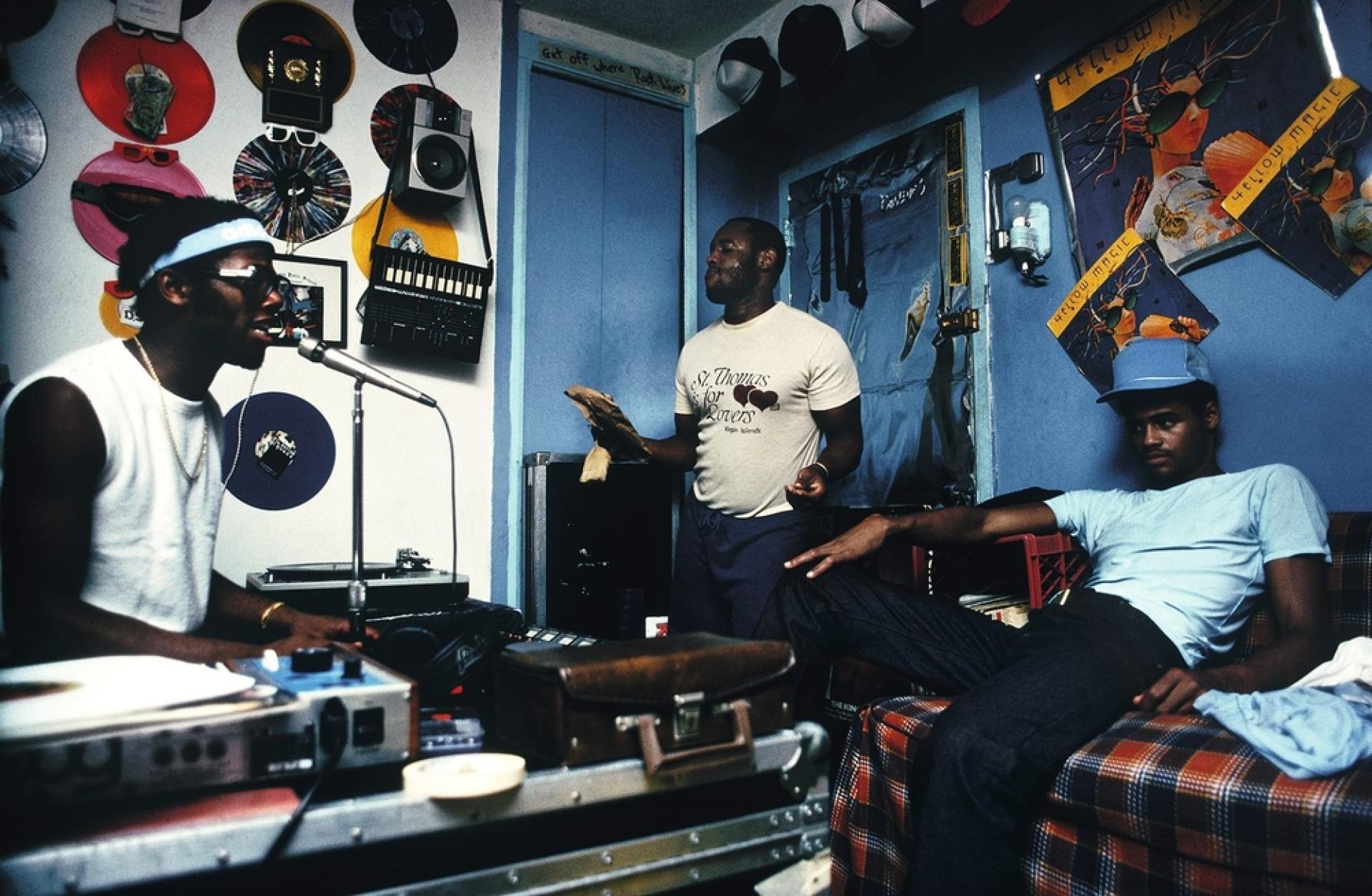 Le DJ D.St en pleine action dans sa chambre, avec des membres de son groupe.