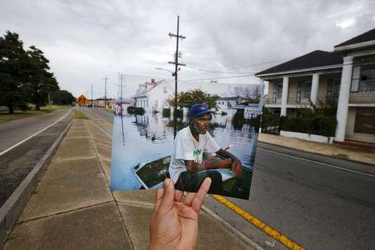 Le photographe Carlos Baria tient une photo qu'il a prise en 2005 lors de l'ouragan Katrina devant le même lieu 10 ans plus tard le 16 août 2015 à la Nouvelle-Orleans.