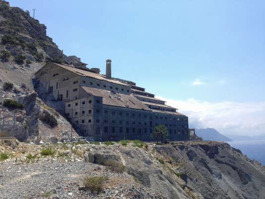 A flanc de colline, au bord de la route pittoresque du Cap Corse, entre montagne et mer, les anciens bâtiments de l'usine paraissent aujourd'hui difficiles à désamianter ou à dynamiter.