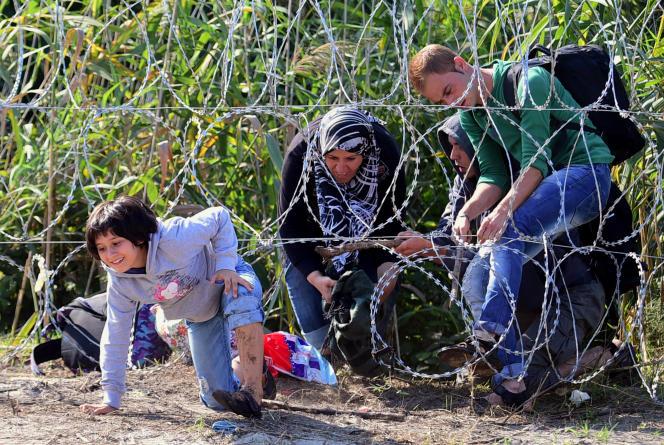 Une famille de migrants se faufile sous la clôture de barbelés installée à la frontière entre la Serbie et la Hongrie, le 28 août.
