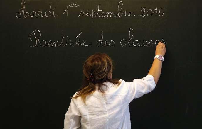 Une enseignante écrit la date du jour au tableau au début de l'année à Pouilly-sur-Serre au nord de la France le 1er septembre 2015.