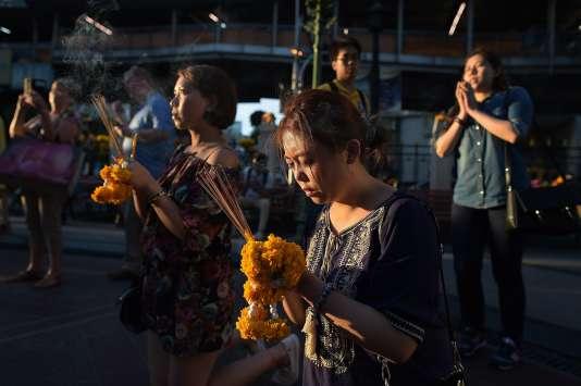 Des habitants priaient pour les victimes de l'attentat meurtrier dans le centre de Bangkok le mois dernier.