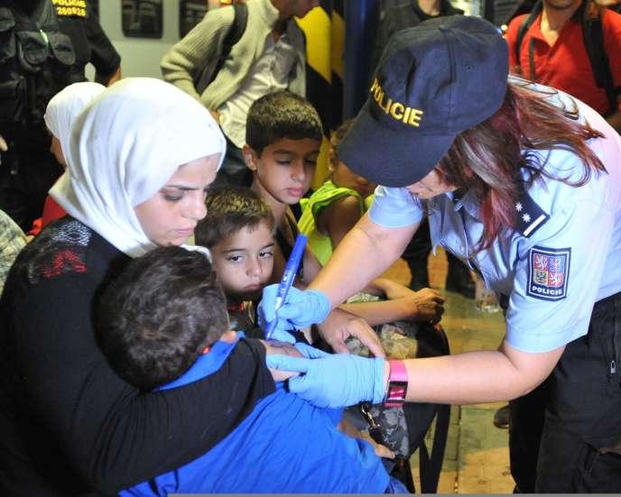 Une policière tchèque inscrit un numéro sur les migrants qui transitent par la gare de Breclav, le 1er septembre.