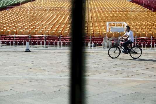 Un cycliste passe devant les sièges en plastique installés place Tiananmen, mercredi 2 septembre, avant le défilé militaire jeudi.