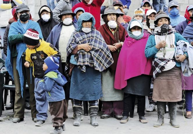 Des Quiténiens masqués pour se protéger des cendres écoutent, le 25 août, le discours du président Rafael Correa sur le plan d'évacuation.