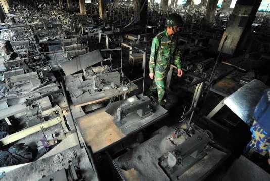 Un soldat des forces armées du Bangladesh marche parmi les machines à coudre carbonisées de l'usine textile Tazreen Fashion, dans la banlieue de Dacca, le 25 novembre 2012.