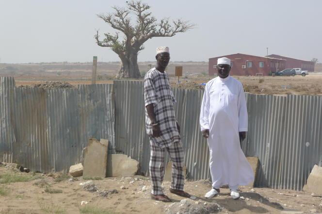 Cheick Faye et Daouda Gueye, membres du collectif local contre la centrale à charbon de Bargny. L'usine sera construite derrière la palissade de tôle.