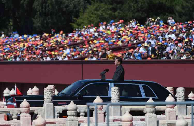 Il a ensuite passé en revue les troupes chinoises, debout dans une limousine sur l'avenue de la Paix céleste.