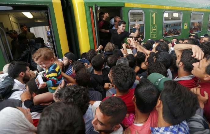 Des migrants tentent de monter à bord d'un train à la garde de Keleti, à Budapest, le 3 septembre.