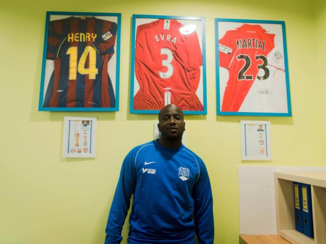 Mamadou Niakaté pose fièrement devant les maillots de trois des anciens pensionnaires du club des Ulis: Thierry Henry, Patrice Evra et Anthony Martial