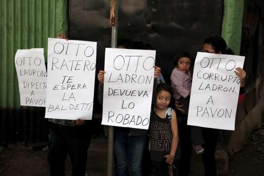 Des Guatémaltèques brandissent des pancartes contre l'ex-président Otto Pérez.