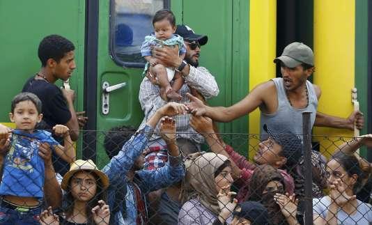 Des réfugiés devant le train dans lequel ils ont passé la nuit à la gare de Bicske, en Hongrie, le vendredi 4 septembre. Ils refusent d'aller dans un camp de transit.