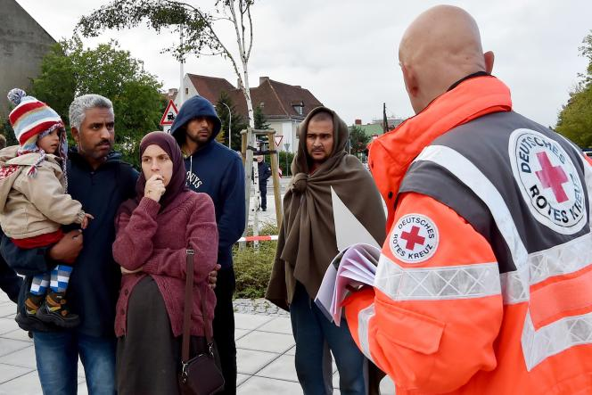 Un membre de la Croix-Rouge allemande accueille des réfugiés arrivant à Eisenhuettenstadt, dans l'Est de l'Allemagne, le 7 septembre.