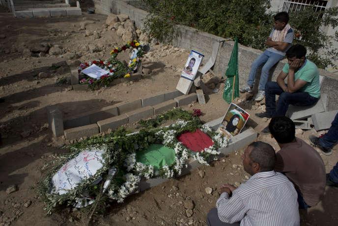 Des palestiniens près des tombes de la famille morte brûlée dans l'incendie criminel de sa maison.
