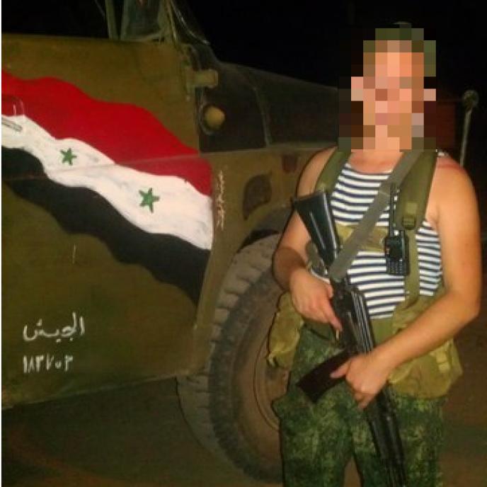 Pavel N., soldat natif de Sébastopol, prenant la pose devant un camion arborant le drapeau syrien.