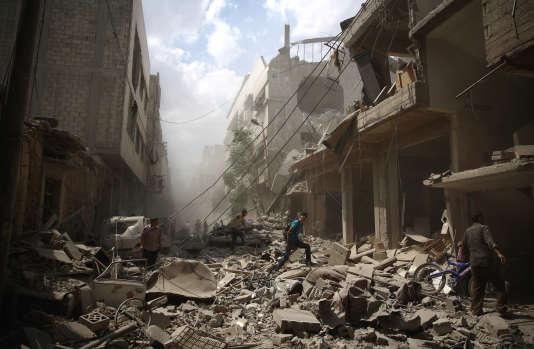 Des habitants dans les décombres de Douma ville syrienne tenue par les rebelles à l'est de Damas, le 30 août 2015.