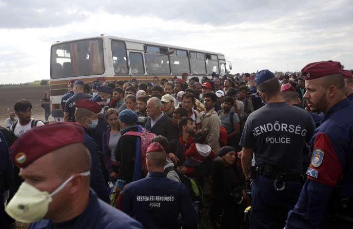 Des policiers Hongrois contrôlent un bus a Roszke en Hongrie en septembre 2015.