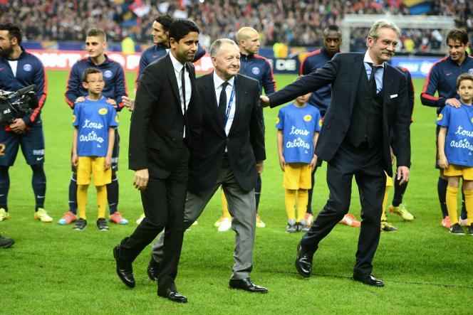 Jean-Michel Aulas entouré du président de la Ligue de football professionnel, Frédéric Thiriez, et de celui du PSG, Nasser Al-Khelaïfi, lors de la finale de la Coupe de la Ligue en avril 2014 au Stade de France.