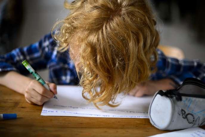 Un enfant fait ses devoirs scolaires à Moudon, en Suisse, en 2013.